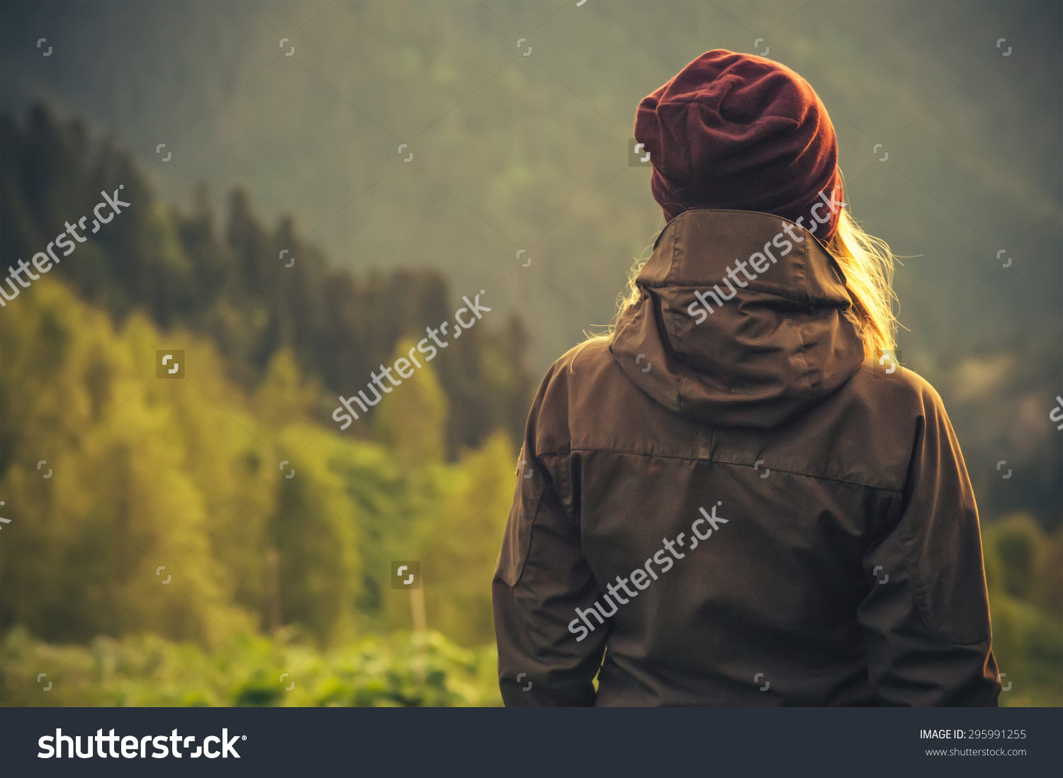 stock-photo-young-woman-standing-alone-outdoor-with-wild-forest-mountains-on-background-travel-lifestyle-and-295991255